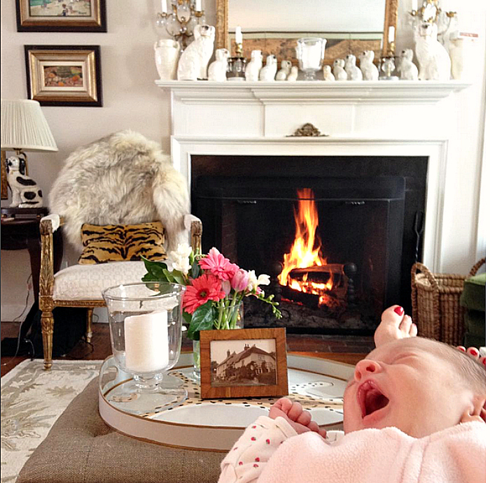Jessika Goranson Lewand with baby in front of fireplace